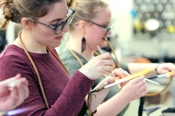 Students blowing glass