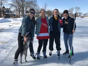 Group of four young people on the snow, wearing ice skates and smiling at the camera