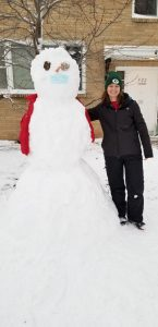Person standing next to a snowman