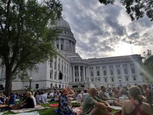 Group of people sitting on the grass with a capitol building in the background