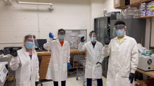 Group of people wearing lab coats and gloves, waving at the camera