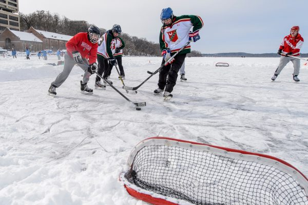Students play hockey on a frozen lake