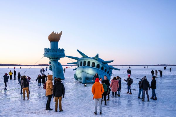 People walk on ice around an inflatable replica of the Statue of Liberty
