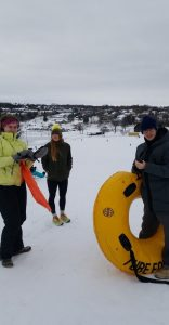 Group of people out in the snow, holding a sled and a tube