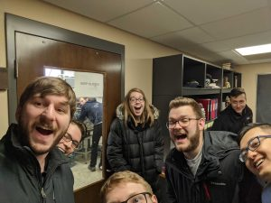 Group of people smiling in a hallway