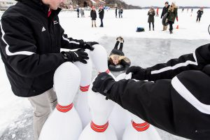 person on innertube heading toward inflatable bowling pins on ice